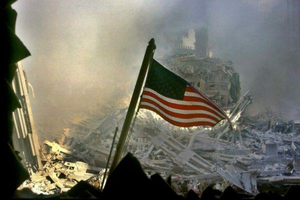 La bandiera americana sventola tra le macerie del World Trade Center a New York, alcune ore dopo l'attentato alle Torri Gemelle crollate a causa dell'impatto di due aerei dirottati dai terroristi islamici sulle Twin Towers, l'11 settembre 2001, New York. ANSA/ EPA/C'sar De Luca