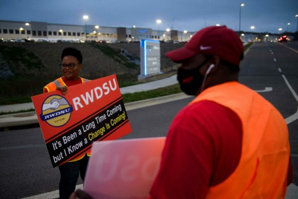 (FILES) In this file photo taken on March 27, 2021, Union organizers Syrena (L) and Steve (no last names given) wave to cars exiting an Amazon fulfillment center in Bessemer, Alabama. - A contentious unionization drive at an Amazon warehouse in Alabama failed as a vote count on April 9, 2021, showed a wide majority of workers rejecting the move. In a vote count seen online, National Labor Relations Board officials counted more than 1,608