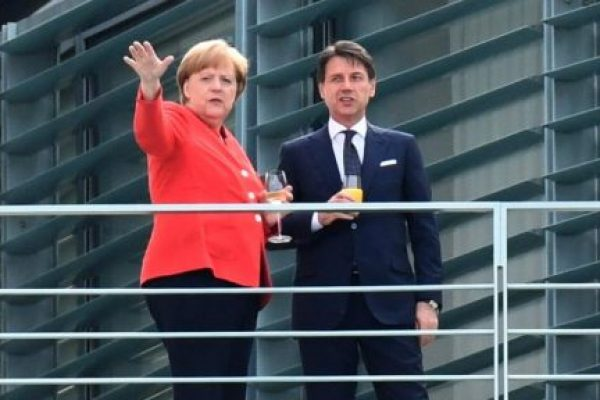 epa06819589 German Chancellor Angela Merkel (L) and Prime Minister of Italy Giuseppe Conte have a drink on a balcony of the Chancellery in Berlin, Germany, 18 June 2018. German Chancellor Angela Merkel and Prime Minister of Italy Giuseppe Conte meet for bilateral talks. EPA/CHRISTIAN BRUNA