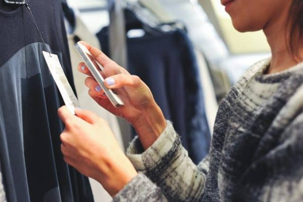 Woman scanning price tag of casual apparels through smart phone at clothes shop, Horizontal shot