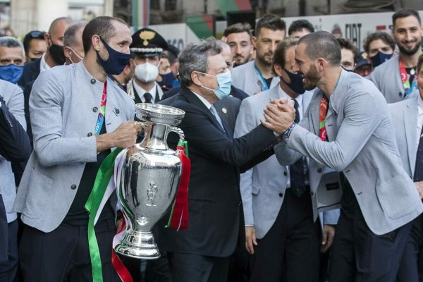 epa09340684 (L-R) Italy's captain Giorgio Chiellini, Italy's Prime Minister Mario Draghi, defender Leonardo Bonucci, and teammates pose with the UEFA EURO 2020 winner's trophy, as players of Italy's national football team arrive to attend a ceremony at the prime minister's office Palazzo Chigi in Rome, Italy, 12 July 2021. Italy won the UEFA EURO 2020 final the previous day. EPA/ROBERTO MONALDO/LAPRESSe / POOL