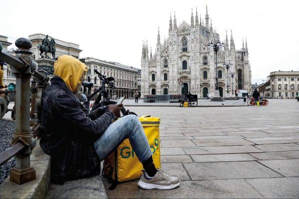 A rider that delivers food rests in Duomo (Cathedral) Square, Milan, Italy, 12 Mrch 2020.Tougher lockdown measures kicked-in in Italy on the day after Italian Premier Conte announced the day earlier that all non-essential shops should close as part of the effort to contain the coronavirus. All of Italy is on lockdown until 03 April due to the novel coronavirus crisis..ANSA/Mourad Balti Touati