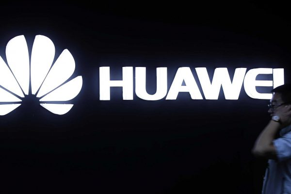 In this May 26, 2016, photo, a man walks past a Huawei logo during a launch event for the Huawei Matebook in Beijing. As trade disputes simmer, Chinese telecommunications giant Huawei, the No. 3 smartphone brand, is shifting its growth efforts toward Europe and Asia in the face of mounting obstacles in the U.S. market. (ANSA/AP Photo/Mark Schiefelbein) [CopyrightNotice: Copyright 2018 The Associated Press. All rights reserved.]