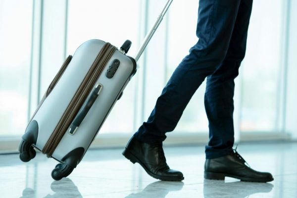 Business,Traveler,Pulling,Suitcase,And,Holding,Passport,And,Airline,Ticket