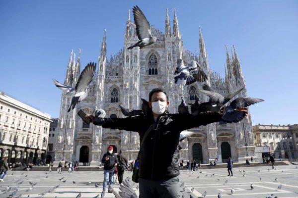 Un turista con la mascherine protettiva in piazza Duomo a Milano, 28 febbraio 2020.ANSA/Mourad Balti Touati