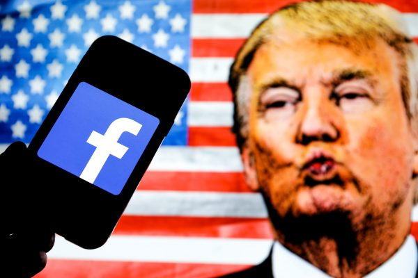 January 7, 2021, Poland: In this photo illustration the Facebook social media app company logo seen displayed on a smartphone, face of Donald Trump and the United States of America flag seen in the background. (Credit Image: © Filip Radwanski/SOPA Images via ZUMA Wire)