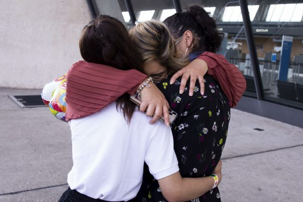 epa09436933 Marcy Barakzai (C) of Alexandria, Virginia, hugs her nieces Marian Barakzai (L ,14 years old) and Mariam Barakzai (R, 17 years old) - both evacuated from Kabul, Afghanistan; after her nieces arrived at Washington Dulles International Airport in Chantilly, Virginia, USA, 30 August 2021. An agreement was reached with the Taliban to allow the coninued evacuation of Afghan allies out of the country after the 31 August withdrawal deadline. EPA/MICHAEL REYNOLDS Permission granted to photograph these minors