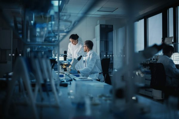 Modern,Medical,Research,Laboratory:,Two,Scientists,Working,,Using,Digital,Tablet,
