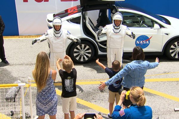 May 27, 2020 - Cape Canaveral, Florida, U.S. - SpaceX Demo-2 crew just walked out of the double doors below the Astronaut Crew Quarters, nd joined a rich legacy. Apollo and space shuttle crews exited through the same doors DOUGLAS HURLEY and ROBERT BEHNKEN just passed through on their way out to the customized Tesla Model X car that will be their ride to Launch Complex 39A. A carefully spaced crowd of family, friends and supporters cheered for the pair as they waved back and paused to speak to their wives and sons. (Credit Image: © NASA/ZUMA Wire/ZUMAPRESS.com)
