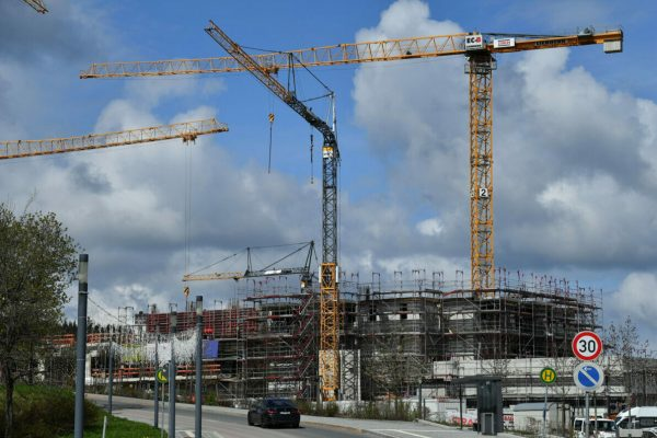 19 May 2021, Thuringia, Oberhof: Cranes rotate above the construction site for a four-star family resort. An entrepreneur from Austria is investing around 50 million euros in the new building. By spring 2022, 110 family suites and 15 chalets will be built in the