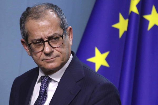 Italian Finance Minister Giovanni Tria walks by the EU flag as he leaves the podium after a group photo of EU finance ministers in Brussels, Monday, Dec. 3, 2018. (ANSA/AP Photo/Olivier Matthys) [CopyrightNotice: Copyright 2018 The Associated Press. All rights reserved]