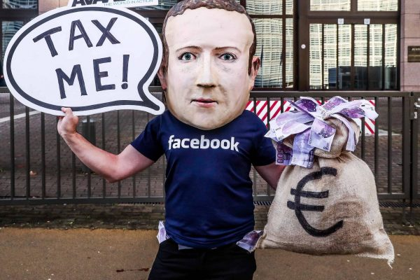 epa07207687 An activist wearing a mask depicting Facebook's CEO Mark Zuckerberg holds a banner reading 'Tax me' at the start of an European Union Finance Ministers Meeting in front of the European Council in Brussels, Belgium, 04 December 2018. Activists ask for an EU tax on big digital firms. EPA/STEPHANIE LECOCQ